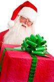 Santa Holding Christmas Present en sus manos en un Backgrou blanco Foto de archivo libre de regalías