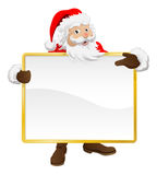 Santa holding Christmas sign and pointing Stock Photos