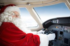 Santa Holding Control Wheel In Cockpit Of Private. Portrait of man in Santa costume holding control wheel in cockpit of private jet Stock Images