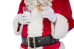 Santa holding cookie and glass of milk Stock Image