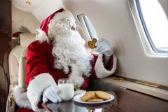 Santa Holding Cookie While Looking Through Private. Man in Santa costume holding cookie while looking through private jet's window Stock Photo