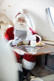 Santa Holding Digital Tablet In Private Jet Stock Photography