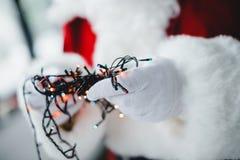 Santa holding festive garland Royalty Free Stock Image