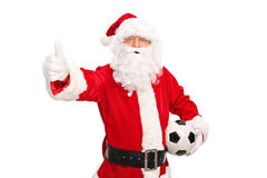 Santa holding a football and giving thumb up Stock Images