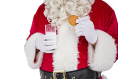 Santa holding glass of milk and cookie Royalty Free Stock Photography