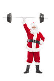 Santa holding a heavy barbell in one hand Royalty Free Stock Photography