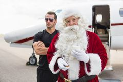Santa Holding Milk Glass By Bodyguard Against. Portrait of Santa holding milk glass while standing with bodyguard against private jet at airport terminal Stock Photo