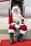Santa Holding Milk Glass While Sitting On Private. Full length portrait of happy Santa Claus holding milk glass while sitting on private jet's ladder Stock Photos