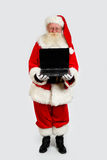 Santa holding a notebook computer Stock Images