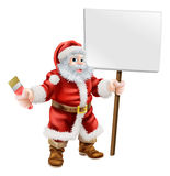 Santa holding paintbrush and sign. Cartoon illustration of Santa holding a spanner and sign, great for decorator or hardware shop Christmas sale or promotion Royalty Free Stock Images