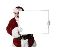 Santa Holding Peeking Around Blank Sign. 3/4 shot of Santa holding a blank white sign Royalty Free Stock Image
