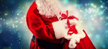 Santa holding a present box from a red sack. In snowy night stock photography