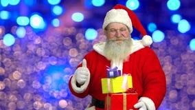 Santa holding presents, thumb up. stock footage