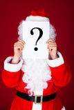 Santa holding question mark in front of his face Stock Images