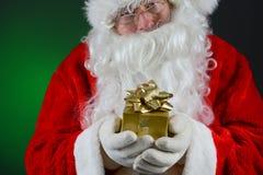 Santa Holding Small Gift Imágenes de archivo libres de regalías