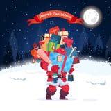 Santa Holding Stack Of Present enferme dans une boîte l'hiver Forest Background Holiday Decoration de nuit de carte de voeux de J Images stock