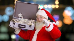 Santa holding suitcase with money. Santa Claus showing thumb up. Christmas and capitalism stock video