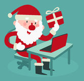 Santa Holding sveglia un regalo al computer Immagine Stock Libera da Diritti