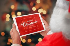 Santa holding tablet with Merry Christmas and a Happy New Year greeting. Bokeh and tree lights in background Royalty Free Stock Photos