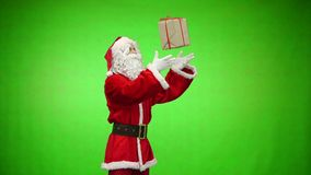 Santa holding two Christmas gifts on green background. Slow motion.  stock video footage