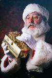 Santa: Holding Up A Wrapped Gift And Reading Name Tag Stock Images