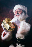 Santa: Holding Up A Wrapped Gift And Reading Name Tag Royalty Free Stock Image