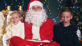 Santa i dzieciaki blisko dekorującej choinki Życzenie lista zbiory