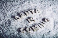 SANTA JEST NADCHODZĄCYM writing na białym śnieżnym tle fotografia stock