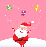 Santa juggling with christmas gifts making heart Royalty Free Stock Photography