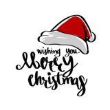 Santa kapelusz i Życzyć ci Wesoło boże narodzenia pisze list kaligrafię, Obraz Royalty Free