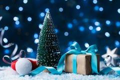Santa kapelusz, jedlinowy drzewo i prezenta pudełko z łęku faborkiem na śnieżnym tle, Boże Narodzenia lub nowego roku kartka z po Fotografia Stock