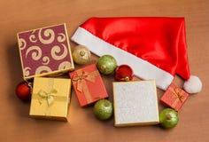 Santa kapelusz, prezentów pudełka i boże narodzenie piłki na drewnianym tle, Obrazy Royalty Free