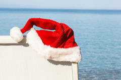 Santa Kapeluszowy obwieszenie na Plażowym krześle. Zdjęcie Stock