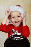 Santa kid. Holiday Boy wearing santa hat Stock Images