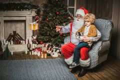 Santa with kid sitting on armchair and using hexacopter drone stock image