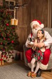 Santa with kid using hexacopter drone. Santa sitting on armchair with kid and using hexacopter drone stock photo