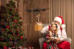 Santa with kid using hexacopter drone. Santa sitting on armchair with kid and using hexacopter drone stock photography