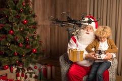Santa with kid using hexacopter drone. Santa with kid sitting on armchair and using hexacopter drone royalty free stock photo