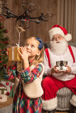 Santa with kid using hexacopter drone. Santa sitting on grey armchair and using hexacopter drone with kid stock photography