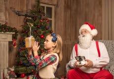 Santa with kid using hexacopter drone. Santa sitting on grey armchair and using hexacopter drone with kid stock photos