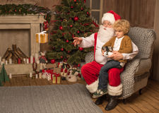 Santa with kid using hexacopter drone. Santa sitting on grey armchair and using hexacopter drone with kid royalty free stock images