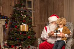 Santa with kid using hexacopter drone. Santa sitting on grey armchair with kid and using hexacopter drone royalty free stock photo