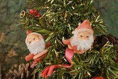 Santa Klaus and Christmas tree. Two little Santa Klaus standing on Christmas' tree Stock Images