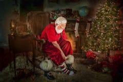Santa Klaus, die auf seine Stiefel sich setzt lizenzfreie stockfotos