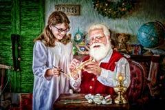 Santa Klaus med en ung flicka arkivfoto