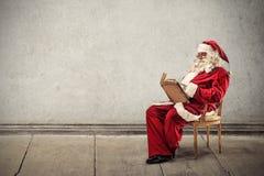 Santa Klaus reading a book Royalty Free Stock Photos