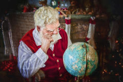 Santa Klaus studying the globe. Santa Klaus studying all the countries of the globe, background a basket of children's toys Royalty Free Stock Photography