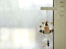 Santa Klaus Toy. Hanging by the frozen window, indoor horizontal closeup Royalty Free Stock Photography