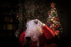 Santa klauzula vaping elektronicznego papieros ubierającego jako tradycyjny Santa na ciemnym stonowanym tle z vape chmurnieje Sel fotografia stock