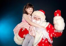 Santa knuffar den hållande flickan på hans arkivbild